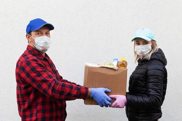 食料の箱が付いている保護マスクのボランティア