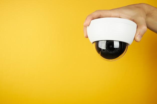 コピースペースのある黄色の手のひらにある待機cctv監視カメラ。セキュリティとプライバシーの概念