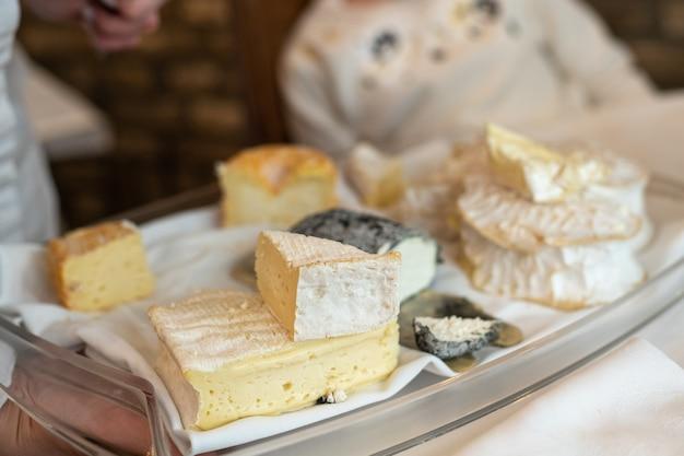 Официант держит тарелку с сырами французской нормандии.