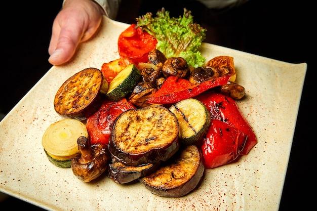 Официант держит тарелку с жареными баклажанами, кабачками, луком, болгарским перцем и грибами.