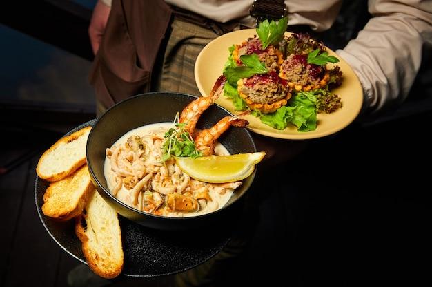 Официант держит тарелку с теплой смесью морепродуктов в сливочном соусе с пшеничным тостом.