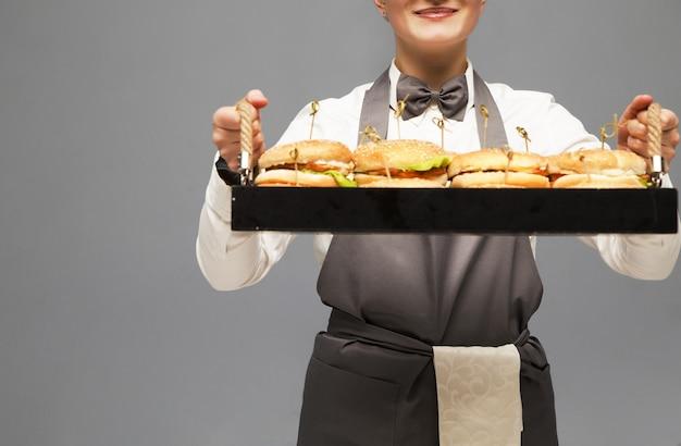 ウェイターはハンバーガーを片手にトレイを持っています。灰色の壁。