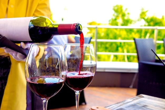 Официант в ресторане на террасе наливает красное вино в бокалы.