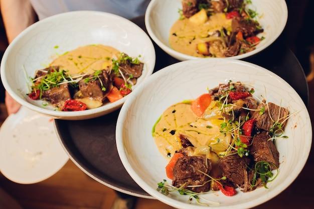 웨이터가 접시를 들고 있습니다 맛있는 육즙이 많은 고기 커틀릿, 채소를 뿌린 으깬 감자, 토마토와 양상추 잎의 신선한 건강 샐러드