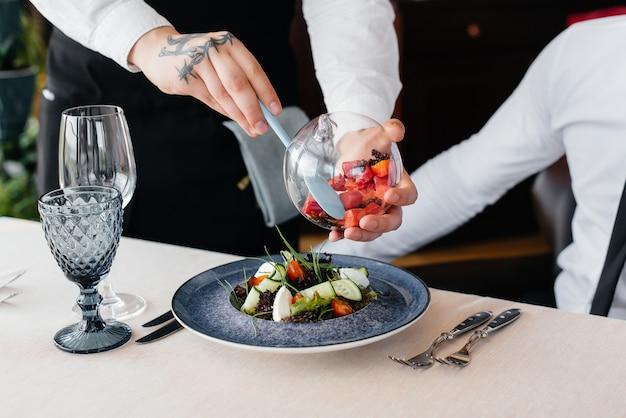 웨이터는 레스토랑의 테이블에 아름다운 서빙에 해산물 샐러드, 참치, 블랙 캐비어를 절묘하게 제공합니다. 고급 요리 클로즈업의 절묘한 진미.