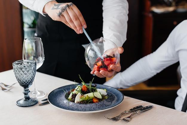 Официант готовит изысканную подачу салата из морепродуктов, тунца и черной икры в красивой подаче на стол в ресторане. изысканные деликатесы высокой кухни крупным планом.