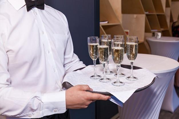 ウェイターはレストランのボトルからグラスにシャンパンを注ぎます。ケータリング、宴会