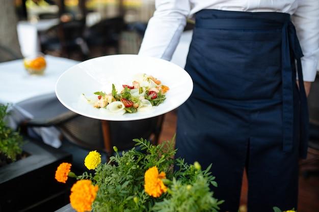 Официант представляет итальянский салат в тарелке.