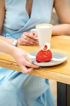 웨이터의 손은 카페에서 여성 고객의 배경에 빨간색 컵 케이크가있는 접시를 테이블에 놓습니다.