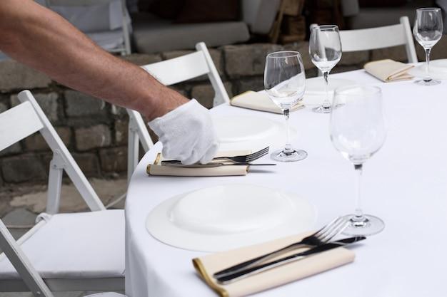 ウェイターは宴会テーブルを提供します。花で飾られた結婚式のテーブルの設定とキャンドルと真鍮の燭台