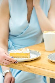 Рука официантки кладет кусок кекса на стол в кафе.