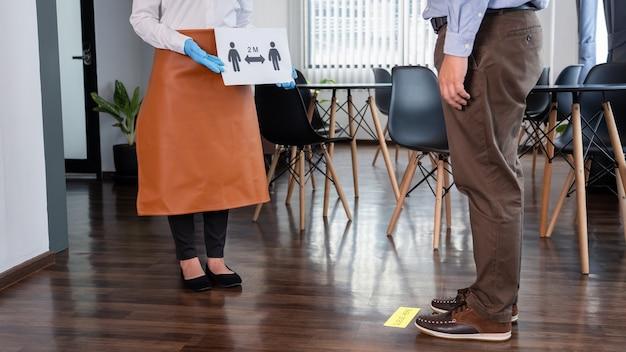 웨이트리스는 고객에게 사회적 거리두기를 설명하는 표지판을 들고