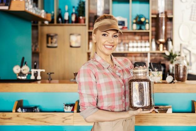Официантка держит стеклянную банку с кофейным зерном. портрет красивой блондинки в современной униформе, готовящейся сделать утренний напиток со свежими кофейными зернами. ресторанная работа, сервис