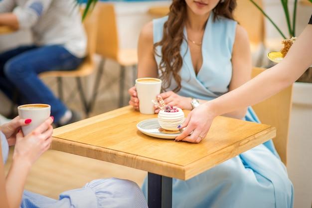 Рука официантки кладет кусок кекса на стол в кафе, женская рука кладет круглое печенье на стол на фоне женщины в синем платье.