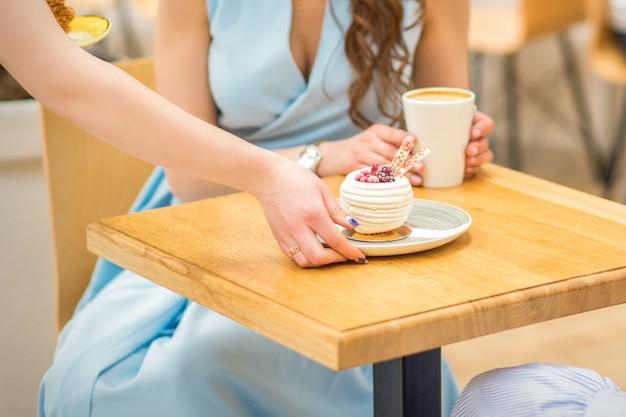 웨이트리스의 손은 카페의 테이블에 컵 케이크 조각을 놓고, 여자 손은 파란 드레스를 입은 여성의 배경에 테이블에 둥근 작은 과자를 넣고 있습니다.