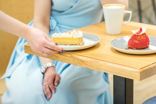ウェイトレスの手がカフェのテーブルにカップケーキを置きます女性の手が青いドレスを着た女性の背景にテーブルに小さなペストリーを置いています
