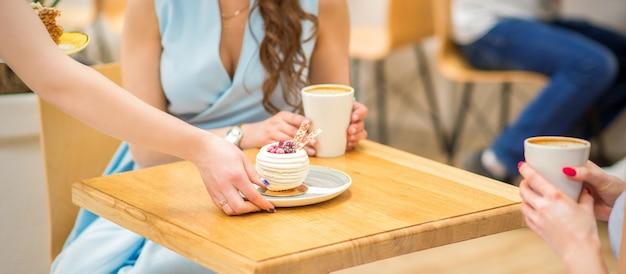 웨이트리스 손은 카페에서 테이블에 컵 케이크 조각을 넣습니다. 여자 손은 파란 드레스를 입은 여성의 배경에 테이블에 둥근 작은 과자를 넣고 있습니다