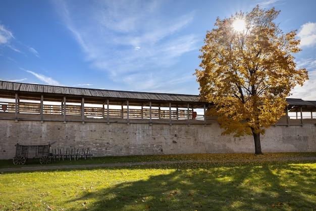 가을에 이즈 보르 스크에있는 중세 요새의 벽. 나무 수레가 요새 벽 근처에 서 있습니다. 노란 잎이 떨어지는 나무