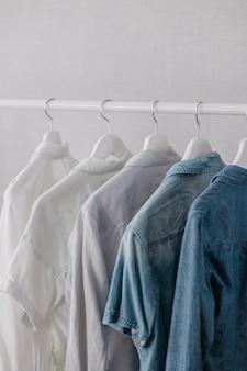 ハンガーに掛かっているワードローブの服は、リビングルームのレールにスタイリッシュなクローゼットの選択
