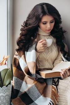 따뜻한 분위기, 휴식의 개념. 검은 머리, 우아한 헤어 스타일, 아름다운 메이크업, 책 읽기, 차 마시는 멋진 소녀.