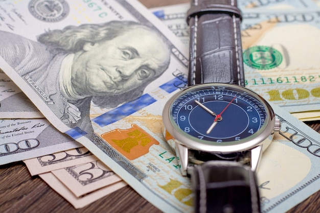 時計はドルの上に横たわっている。お金を稼ぐ時間。時は金なり