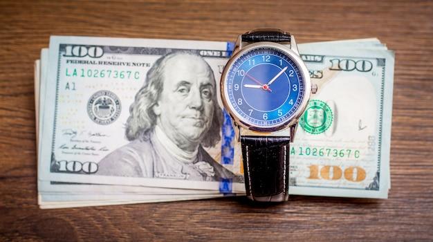時計はドルの上に横たわっています