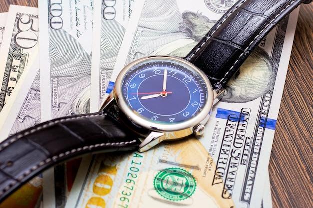 Часы лежат на долларах Premium Фотографии