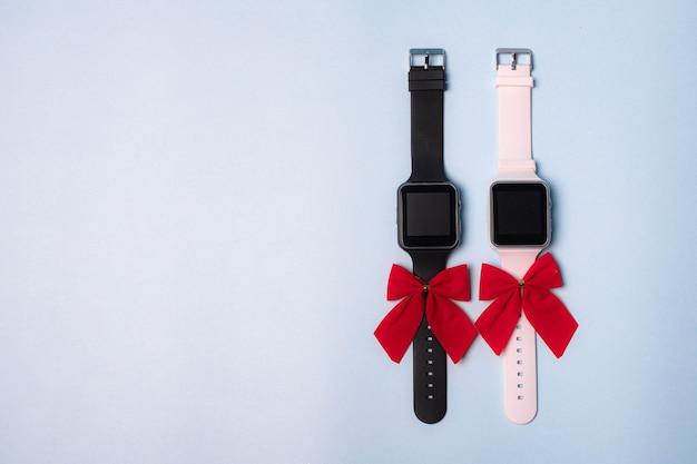 時計は白と黒の電子式で、無地の背景にリボンが付いています