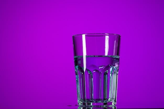 Вода в стакане на сиреневом фоне