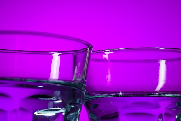Вода в двух стаканах на сиреневом фоне