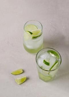 水はミネラルで、透明なグラスにライムと氷が入っています。体のデトックスのための冷たい飲み物、スペースのコピー
