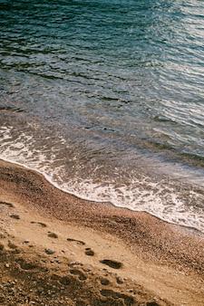 Волна накатывает на пляж, где видны следы человеческих ног.