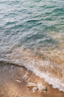 Волна накатывает на пляж, на котором лежат камни