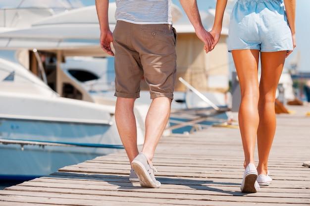 진정한 사랑의 길. 부두를 따라 걷는 동안 손을 잡고 젊은 부부의 클로즈업