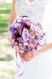 흰색 신부 레이스 웨딩 드레스 위에 신부의 손에 라일락 장미, 유스토마, 백합이 있는 웨딩 부게