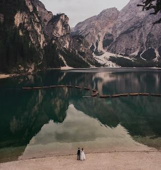 結婚式のカップルは、湖岸の高い石の山に立っています