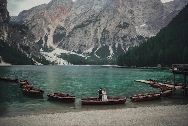 Свадебная пара стоит на берегу огромного широкого прозрачного бирюзового аквамаринового зеленого озера.