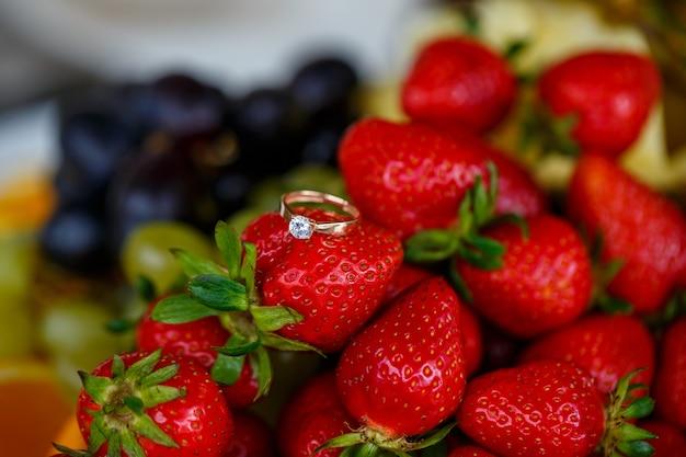 結婚指輪は赤い熟したイチゴの上にあります。夏の美味しいベリー