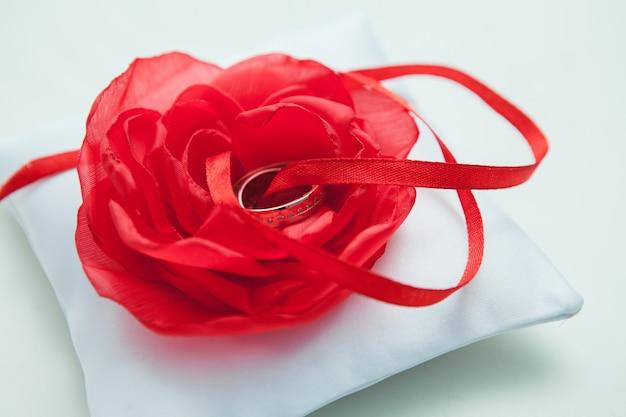 赤い紙の花の結婚指輪がクローズアップ