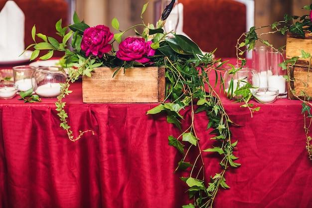結婚式のテーブルは、牡丹、ツタの小枝、キャンドルで飾られています。素朴なスタイル。