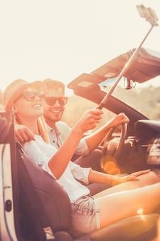 Селфи на выходных. низкий угол обзора радостной молодой пары, делающей селфи, сидя в кабриолете