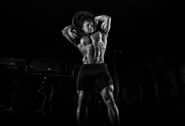 Тяжелоатлет выполняет тренировку с отягощениями. он поднял над головой тяжелый блин и совершает круговые движения бедрами. передний план