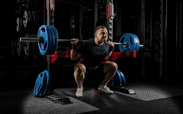 重量挙げ選手は重いバーベルで立つ準備をしています。