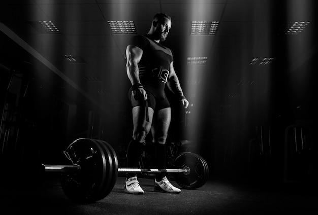 重量挙げ選手は、デッドリフトと呼ばれる運動を行う準備をしています。彼はバーベルの真上に立ってそれを見ます。