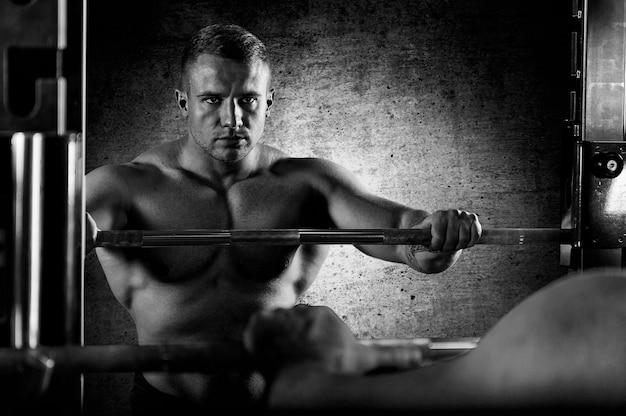 重量挙げ選手はバーベルに手を置き、鏡で自分自身を見ます。鏡の中の反射