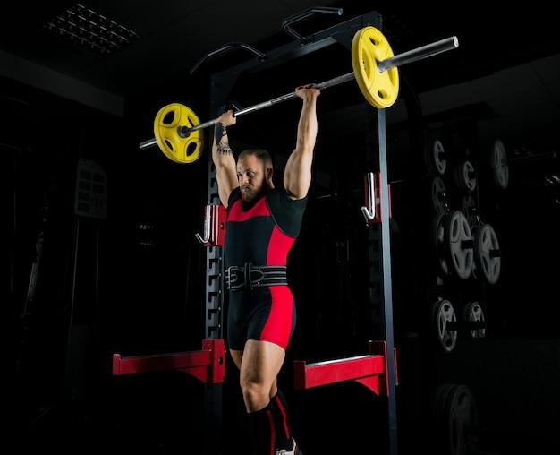 Тяжелоатлет поднимает штангу над головой и фиксирует вес