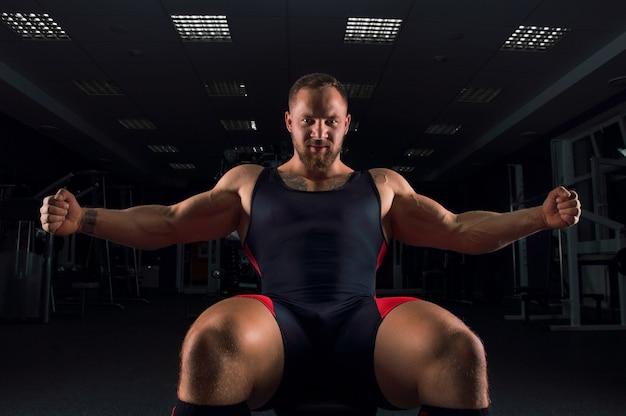 Тяжелоатлет сидит на скамейке в тренажерном зале с раскинутыми руками и улыбается