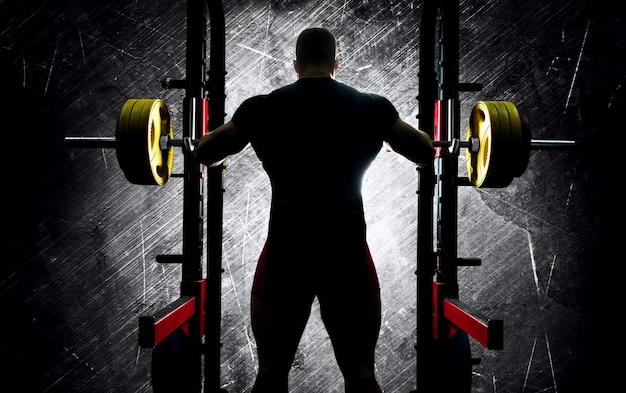 重量挙げ選手は、重いバーベルの後ろに両手を置いて立っています。背面図