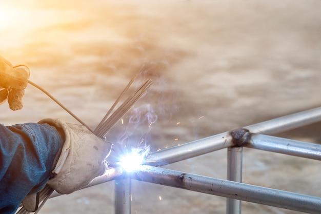 용접공이 강철 프레임을 용접하고 있습니다. 노동과 산업은 열심히 일합니다.