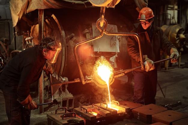 용접기는 공장 상점에서 금속을 녹이는 두 명의 철강 노동자에서 일합니다.